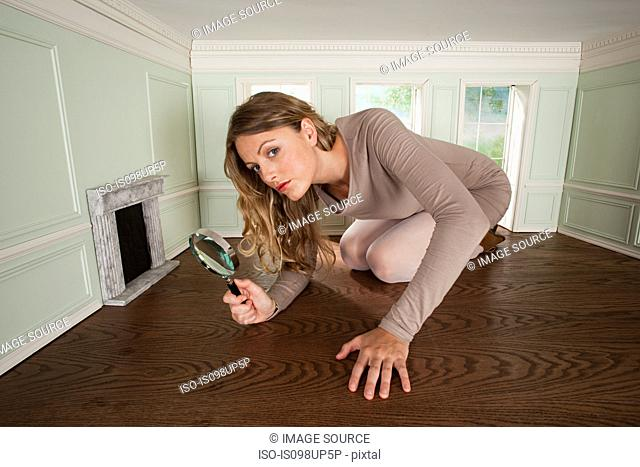 Young woman in small room with magnifying glass