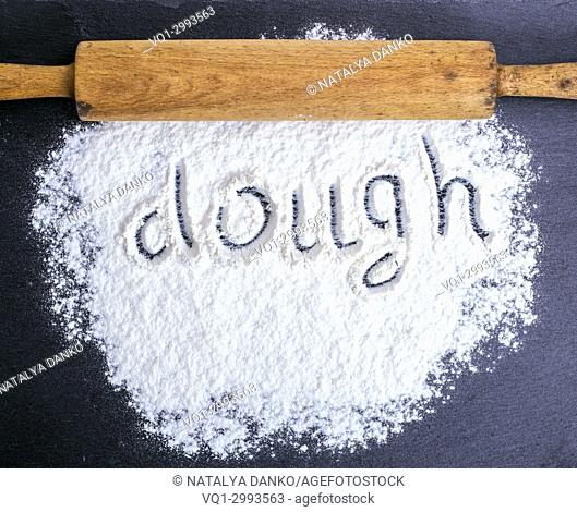 scattered white wheat flour and a wooden rolling pin, inscription dough