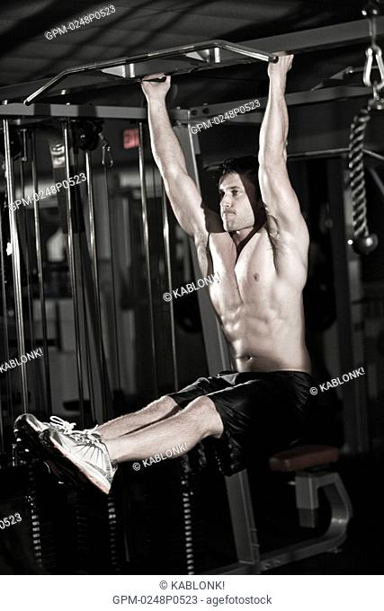 Young man hanging on rod in gym with exercising equipment in background