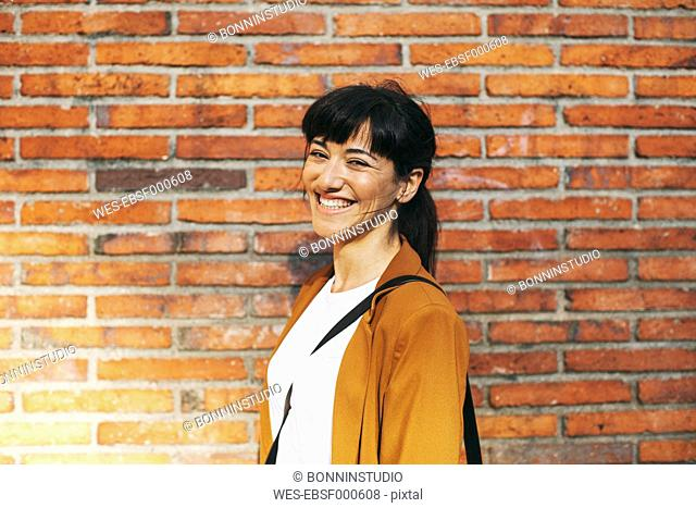 Portrait of laughing businesswoman in front of a brick wall