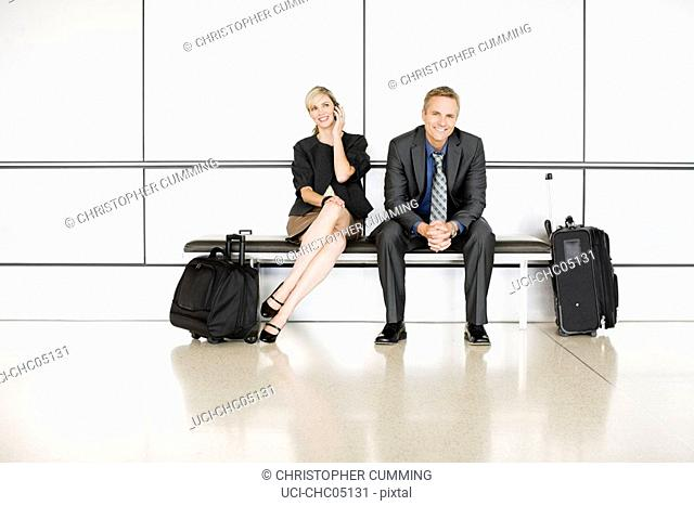 Businesspeople next to suitcases