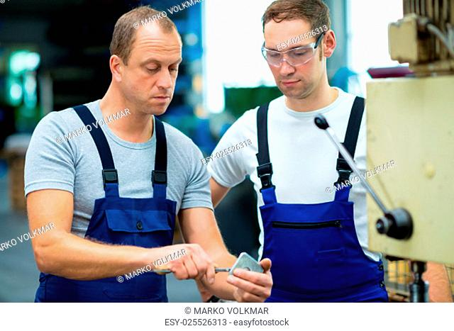 two young worker in factory on the machine