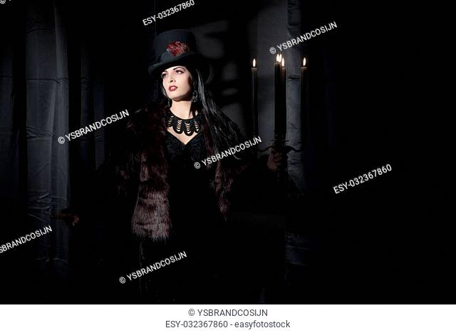 Dark mysterious witch fashion woman. Black curtains with window shadow on wall