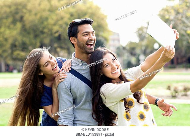 Smiling friends taking photograph with digital tablet in park