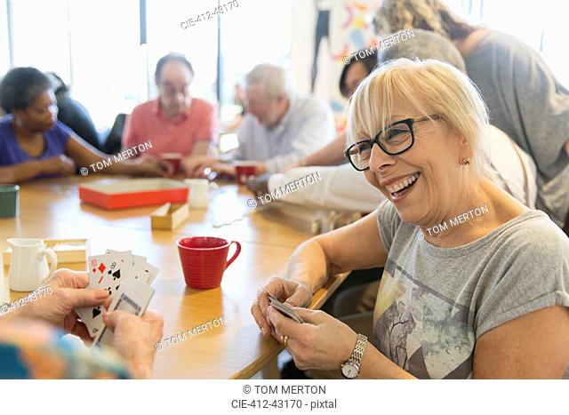 Happy senior woman playing cards with friend at table in community center