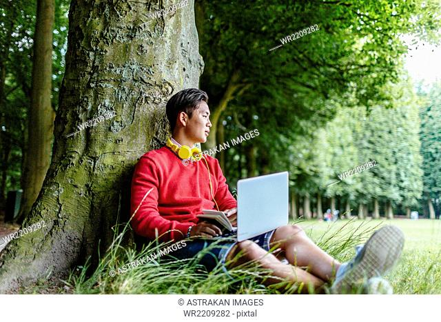 Full length of young man with book and laptop leaning against tree at park