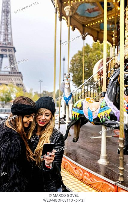 France, Paris, two best friends using their smartphone at a carousel with the Eiffel Tower in the background