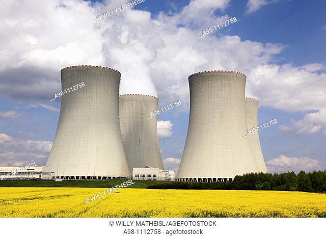 landscape showing 4 cooling towers of Temelin nuclear power plant station and yellow rape field, Czech Republic, Europe
