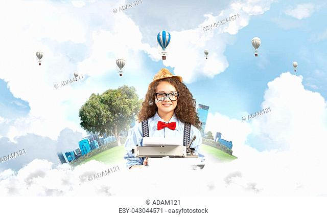 Young and beautiful woman writer in hat and eyeglasses using typing machine while sitting at the table with floating city island and cloudy skyscape with flying...