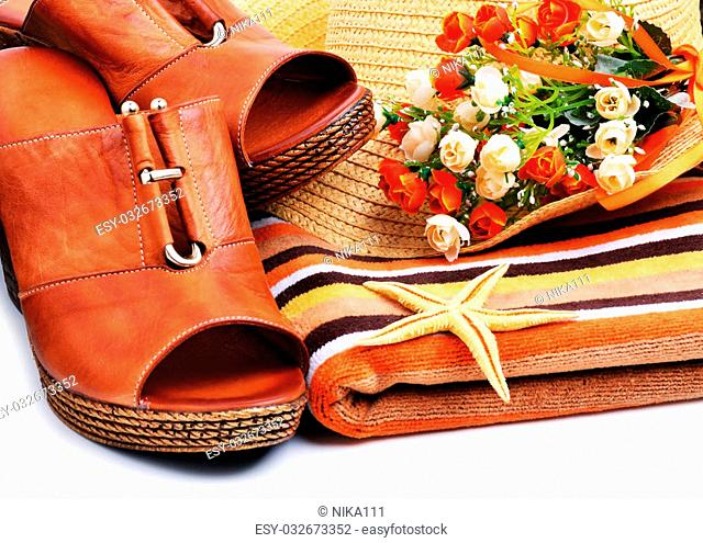 Leather woman shoes decorated with starfish, towels, beach hat isolated on white