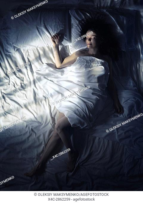 Artistic overhead photo of a young woman sleeping alone in bed at night in dark bedroom lit by moonlight