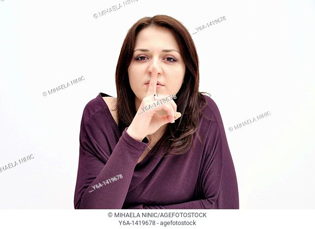 Young woman holding finger up to mouth