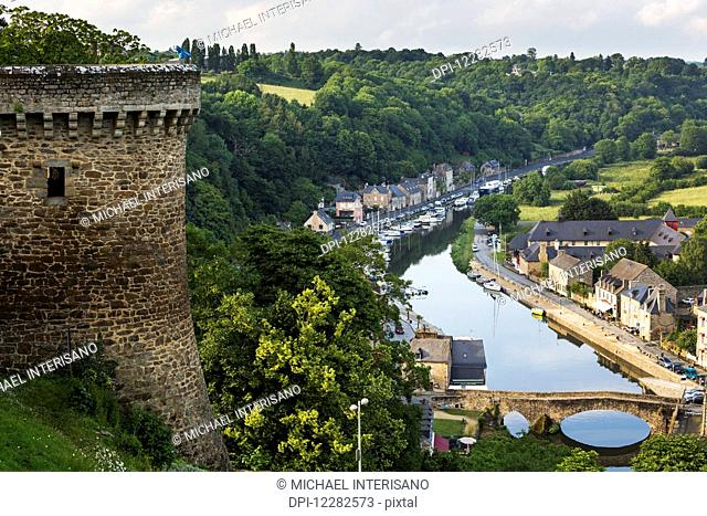 Fortress stone wall turret overlooking riverside treed valley town with stone bridge; Dinan, Brittany, France
