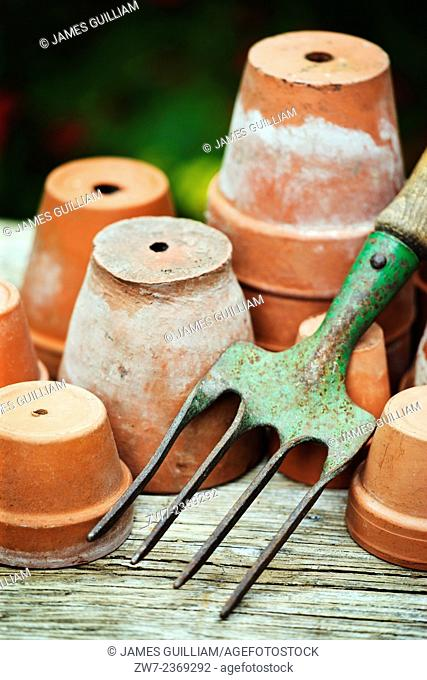 Terracotta plant pots with hand fork