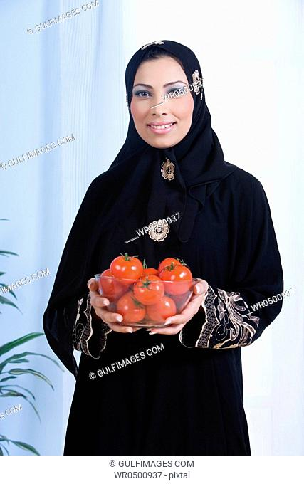 Young woman holding bowl tomatoes in bowl, portrait