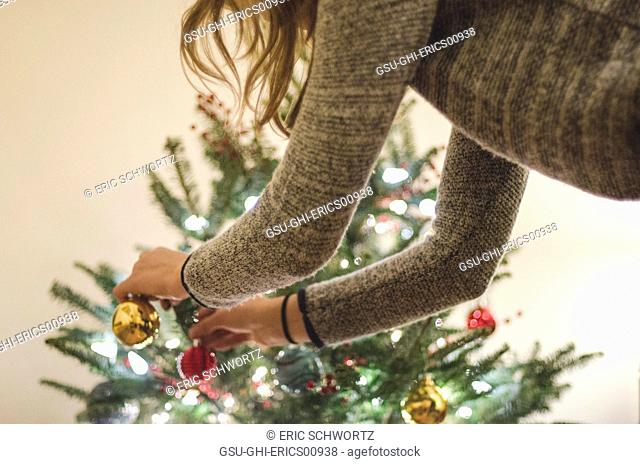 Young Woman Placing Ornaments on Christmas Tree