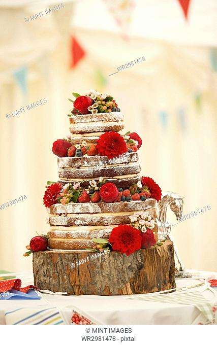 Close up of a wedding cake decorated with strawberries and cream and fresh red flowers, dahlias set on a wooden log