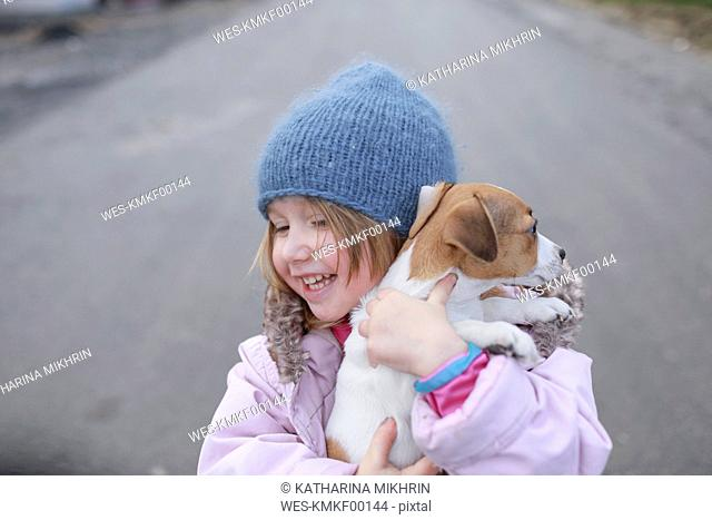 Happy little girl holding Jack Russel Terrier puppy