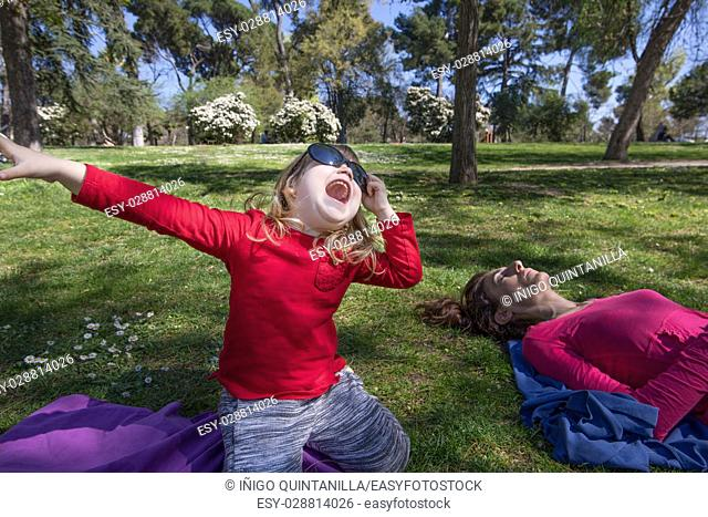 three years old blonde child, with red shirt, sitting on knees in green grass in park, next to mother sleeping, with big adult woman sunglasses singing or...