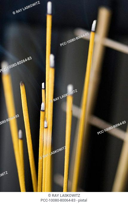 Close-up of the burning incense that adorns a Buddhist shrine