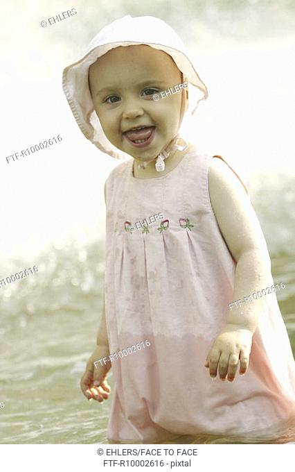 Little girl paddeling in a fountain
