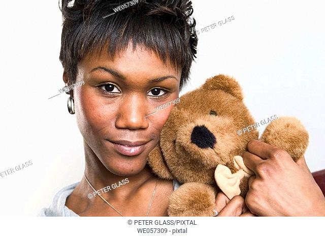 Young black woman posing with a teddy bear