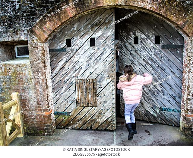 Preteen caucasian girl trying to push an old wood heavy door in an old Fort. Fort Macon State Park, originally called, Fort Dobbs then Fort Macon Military...