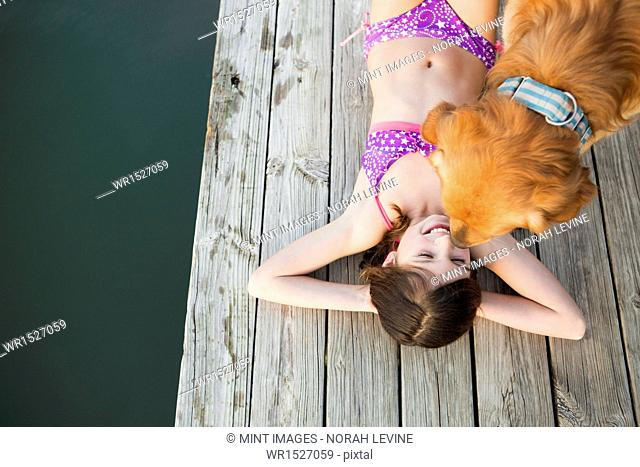 A young girl and a golden retriever dog on a jetty