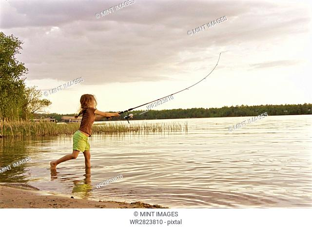 A young girl standing in the shallow water of a lake fishing with a rod