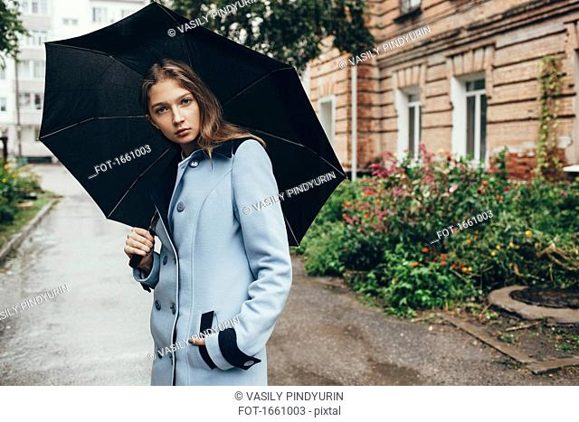 Portrait of teenage girl holding umbrella standing on street in town