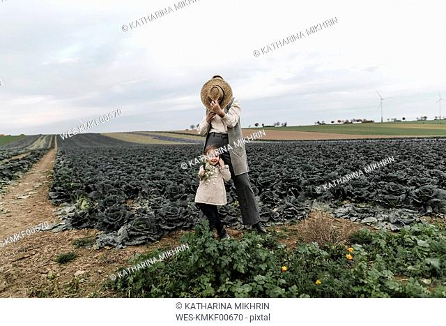 Girl and her mother with straw hat and flowers at a cabbage field