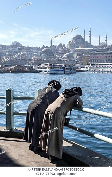 Two traditionaly dressed turkish women admire the view from the Galata bridge across the Golden Horn toward the Suleymaniye mosque and the Istanbul skyline