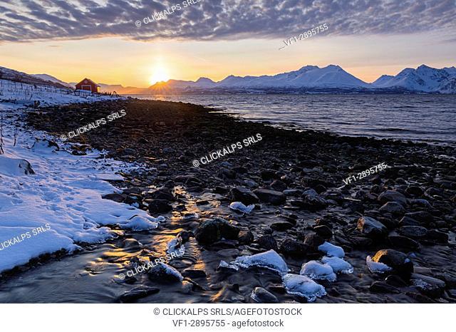 The sun sets behind the Lyngen Alps. Nordmannvik, Kafjord, Lyngen Alps, Troms, Norway, Lapland, Europe