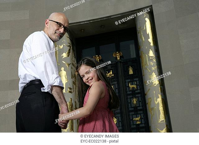 mature man holding hands with girl, looking at camera