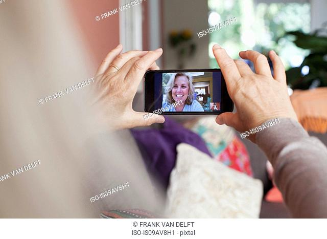 Senior woman, holding smartphone, on video call with friend