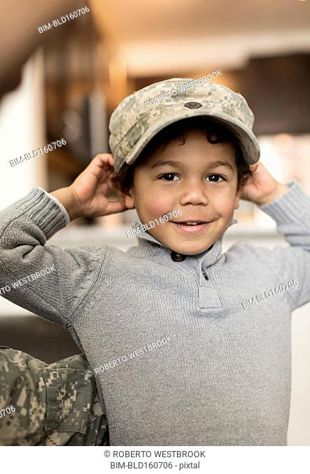 Mixed race boy wearing soldier cap