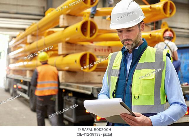 Male foreman reading paperwork on clipboard in factory