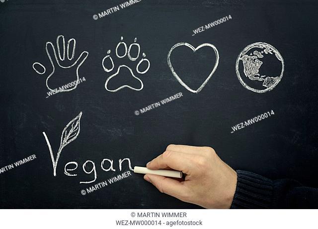 Man drawing vegan concept on blackboard, close-up
