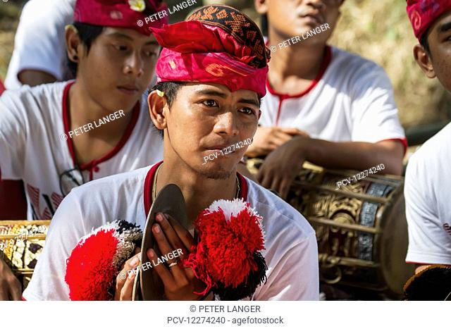 Man in a gamelan ensemble preforming during a Ngaben or Cremation Ceremony, Klungkung, Bali, Indonesia