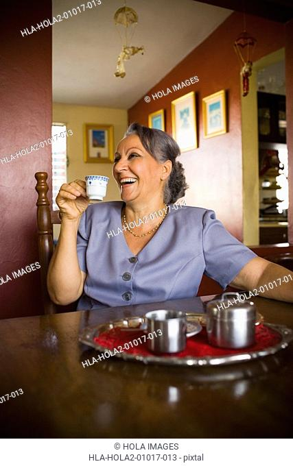 Mature woman holding a cup of tea and smiling