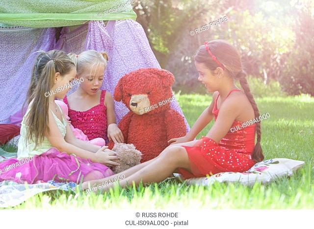 Three girls playing with teddy bears in garden