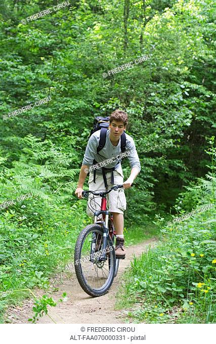 Man riding bicycle through woods