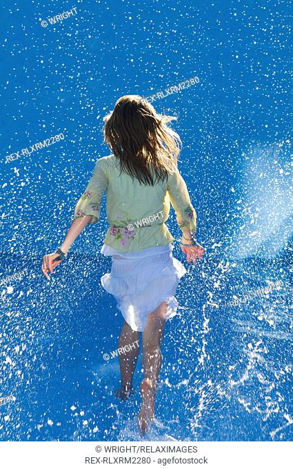 Girl (10-11) running in water in empty swimming pool, Grainau, Germany