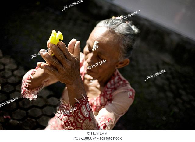 Woman praying during Kuningan Festival; Bali, Indonesia