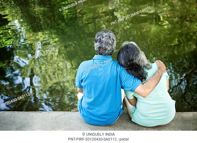 Mature couple sitting in a park at the lakeside, Lodi Gardens, New Delhi, India
