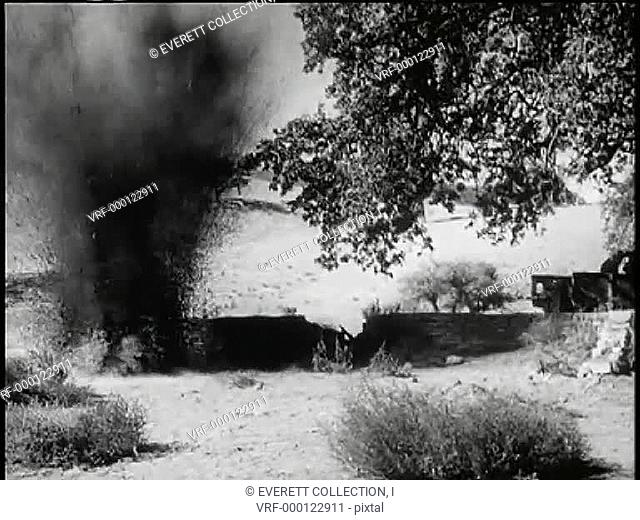 Wide shot bomb exploding near soldiers crouching behind low wall