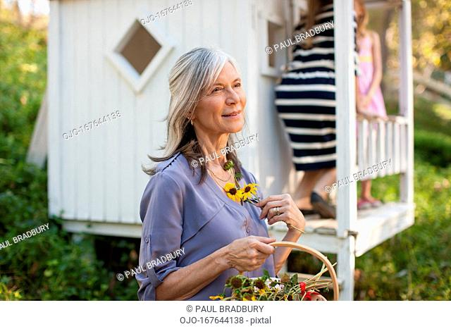 Older woman picking flowers outdoors