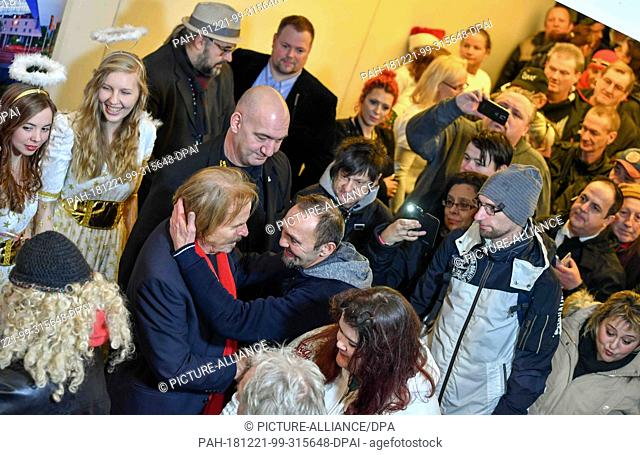 21 December 2018, Berlin: The singer Frank Zander (l) welcomes his guests in the Hotel Estrel at the traditional Christmas dinner for people from the street