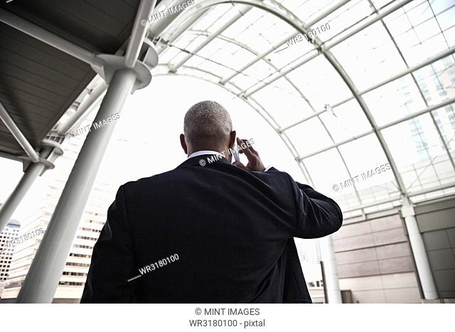 Black businessman on the phone while walking through a large glass covered walkway