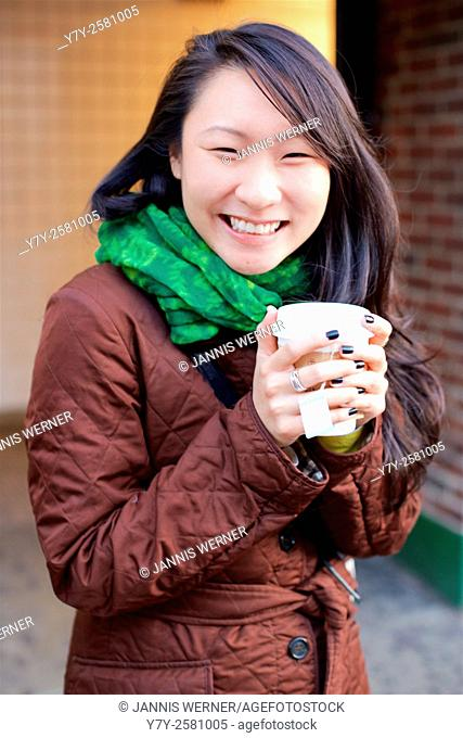 Young Asian woman smiles at the camera while warming her hands with tea in a paper cup in the winter streets of Manhattan